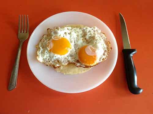 Coloca los huevos en un plato sobre las tortillas fritas
